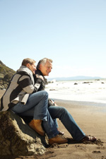Senior Couple Sitting on a Rock at the Beach